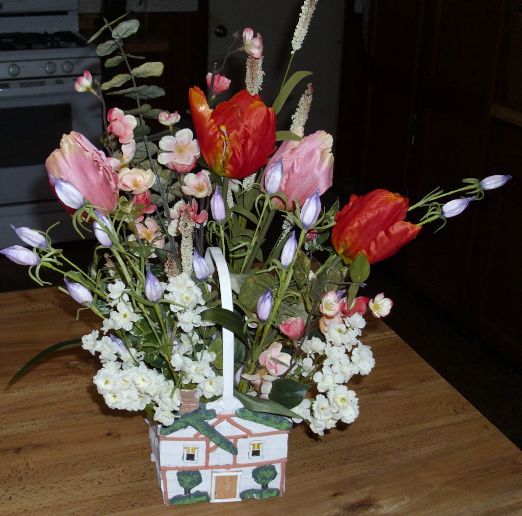 A flower basket in the shape of a house with a springtime arrangement.