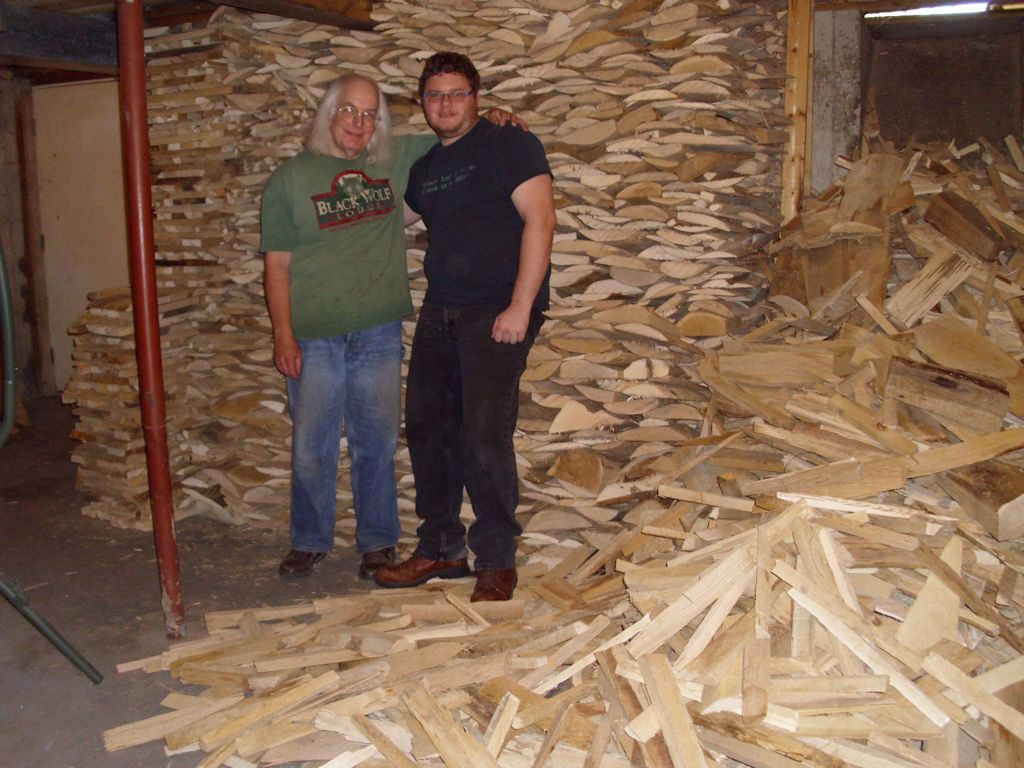 John and Braden standing next to a huge pile of wood.